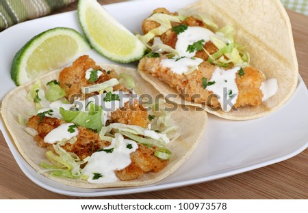 Two fish tacos with sliced lime on a plate - stock photo