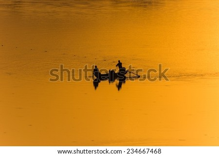Two fishermen fishing on a lake in Sri Lanka while the setting sun illuminates their fishing grounds - stock photo