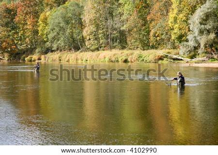 two fishermen in river fishing - stock photo