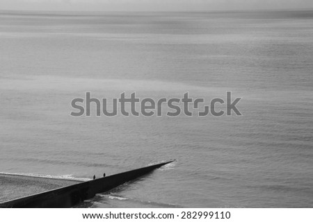 Two fishermen on old concrete pier. Mers-les-Bains (Picardy, France) Aged photo. Black and white. - stock photo