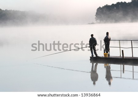 Two fishermen waiting for a fish on misty morning - stock photo