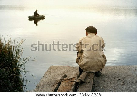 Two fishermen - young man sitting in a boat, and an old man on the shore - stock photo