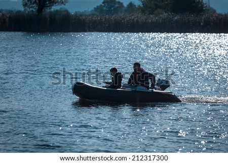Two fishermens, father&son in the powerboat on the river. - stock photo