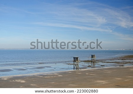 Two fishing cabins stands on the beach close to the atlantic ocean. The sky is blue with a few white thin clouds - stock photo