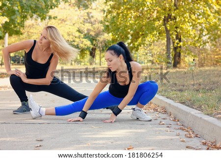 Two fit athletic young woman working out together on a road in a park doing stretching exercise and leg extensions to improve suppleness and mobility - stock photo