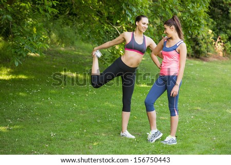 Two fit happy friends stretching before a run in park in the sunshine