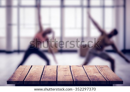 Two fit people doing fitness against wooden floor - stock photo
