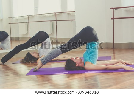 Two fit pretty women are stretching back together - stock photo