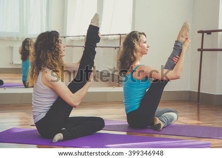 Two fit pretty women are stretching legs together - stock photo