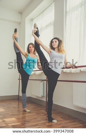 Two fit women are doing ballet exercise