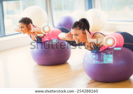 Two fit women exercising on fitness balls in gym against fitness interface - stock photo