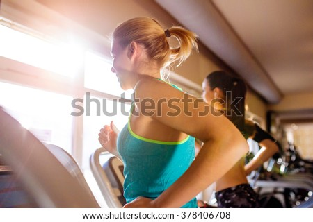 Two fit women running on treadmills in modern gym - stock photo