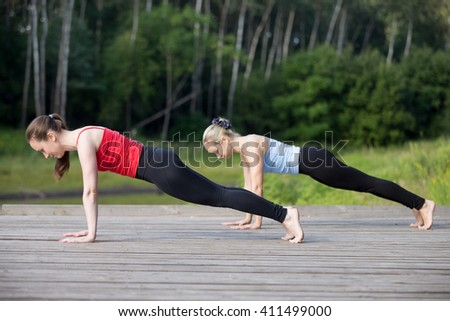 Two fit young beautiful women working out outdoors in park on summer day, wearing sportswear red and blue tank tops, doing plank or phalankasana posture for abdominal muscles, full length - stock photo