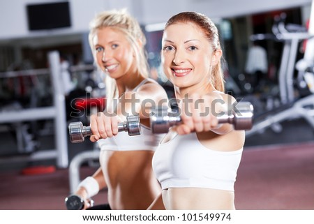 two fitness woman doing dumbbell workout - stock photo
