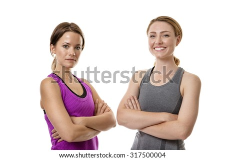 two fitness woman stand next to each other looking at the camera