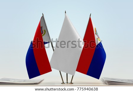 Two flags of Sint Maarten with a white flag in the middle