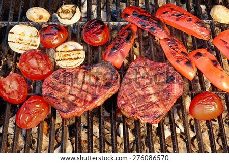 Two Flame Broiled Beef Steaks And Vegetables On BBQ Grill Close-up. Good Food For Outdoor Summer Barbecue Party Or Picnic - stock photo