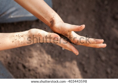 Two flattened caucasian hands treating soil carefully - stock photo