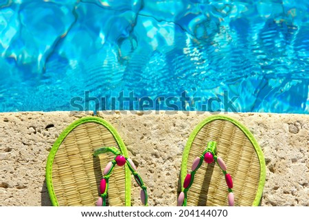 Two flip flops on the platform beside swimming pool - stock photo