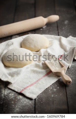 Two floured balls of uncooked homemade pizza dough on a kitchen towel on a rustic dark wooden table with flour and rolling pin. - stock photo