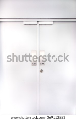 two flush doors with metallic push sign and door knob