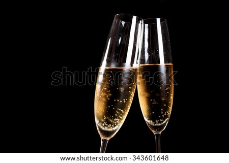 Two flutes of champagne on black background - stock photo