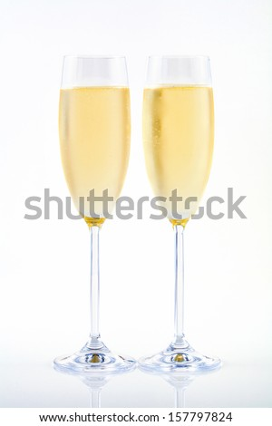 Two flutes of champagne on white