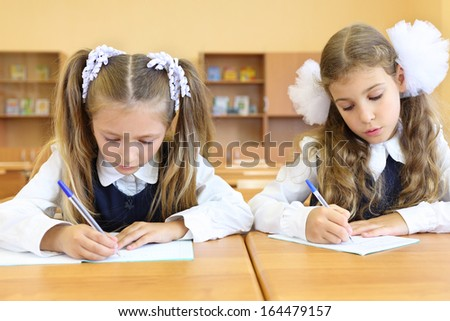 Two focused girls in uniform sit at wooden school desk and learn to write in classroom at school.