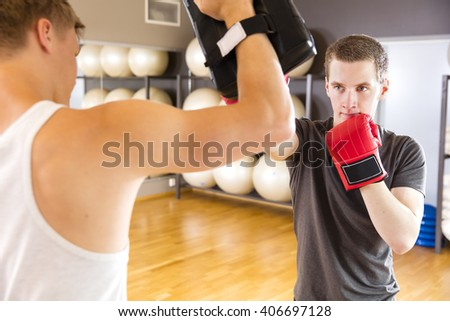 Two focused men training boxing at the fitness gym - stock photo