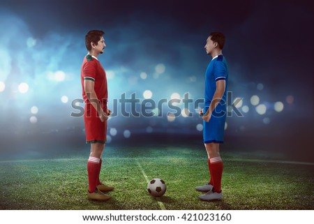 Two football player facing each other on the kickoff at the stadium - stock photo