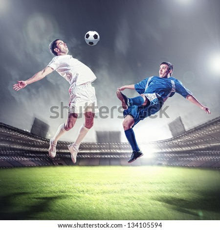two football players in jump to strike the ball at the stadium - stock photo