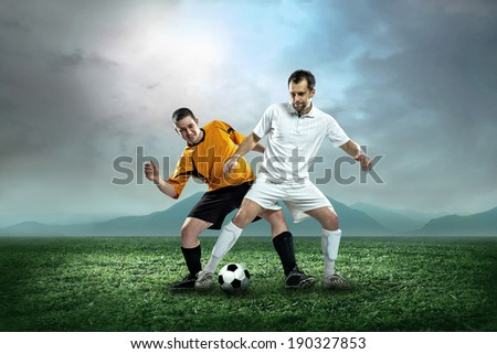 Two football players with ball in action outdoors.