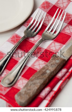 Two forks and a knife on a red and white checkered napkin. Informal table setting. - stock photo