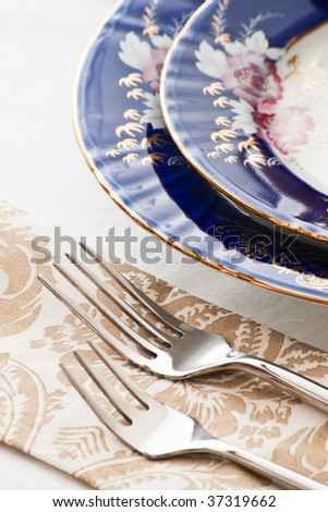two forks and fine porcelain plates - stock photo
