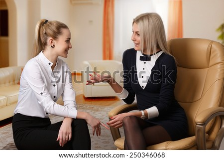 Two formal dressed elegant women talking each other in relaxed atmosphere. Chatter, dialogue,conversation concept. Girlfriends gossip - stock photo