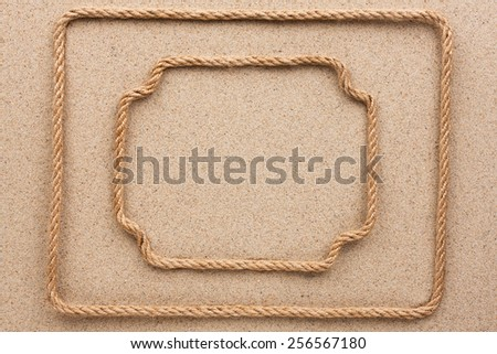 Two frame made of rope lying on the sand, for your text, pictures, photos - stock photo