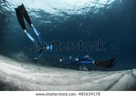 Two free divers finning over the sandy sea bottom. Athletes are completely out of focus