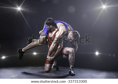Two freestyle wrestlers in red and blue uniform wrestling against the lights on background - stock photo