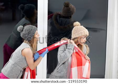 Two freezing girls are fighting for a blanket - stock photo