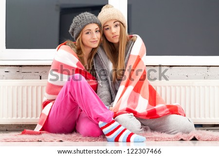 Two freezing girls near the heater