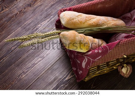 Two French bread with spikelets  lying in a wicker basket.