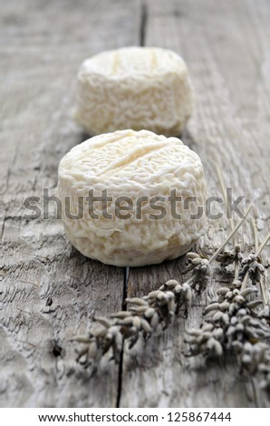 Two french goats cheeses on wooden background with lavendar - stock photo