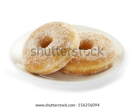 two fresh and delicious tasting donuts served on a white plate sprinkled with some sweet powder sugar - stock photo