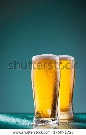 Two fresh beer glasses against vivid orange background - stock photo