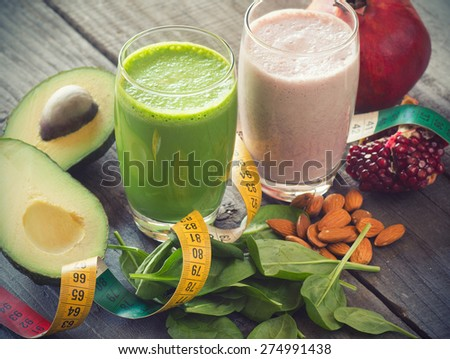two fresh blended fruit smoothies made with avocado, pomegranate, spinach and almonds - stock photo