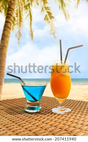 Two fresh cocktail on a beach under palm tree. - stock photo