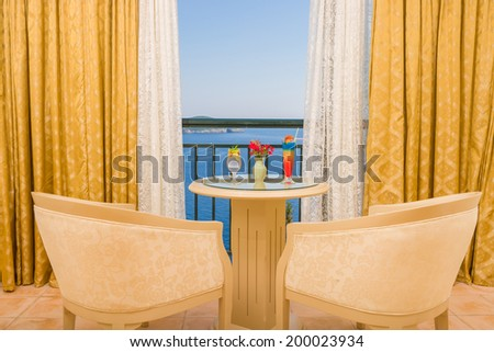 Two fresh cocktails in the hotel room with sea view - stock photo