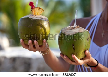 Two fresh coconut cocktails in woman hands. Healthy lifestyle concept.