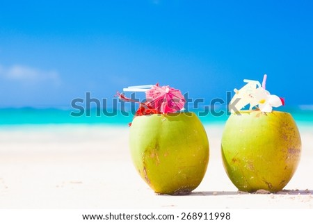 two fresh coconut cocktails on tropical beach. caribbean - stock photo