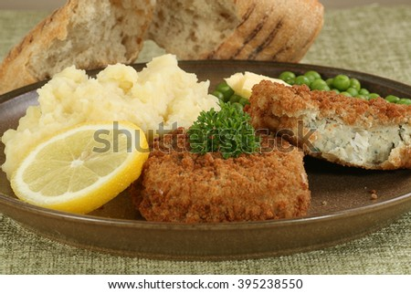 two fresh cod fishcakes with mashed potato and peas - stock photo